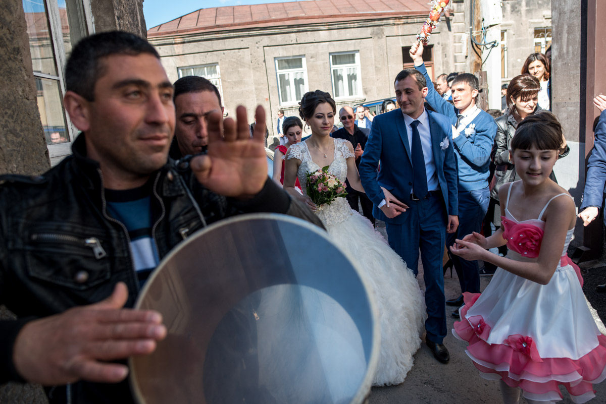 musician plays the drum to welcome bride and groom into their home after Armenian wedding ceremony