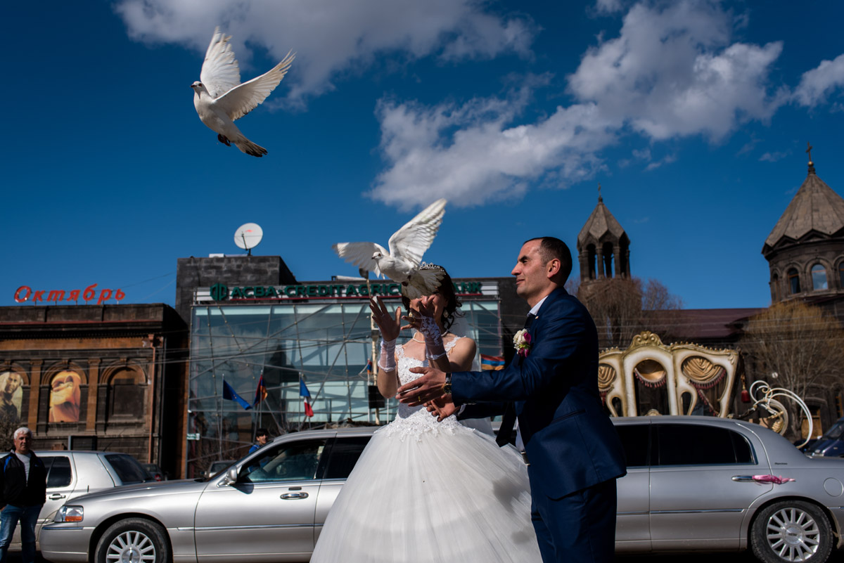 armenian newly weds release two white doves after their wedding ceremony in Gyumri in armenia
