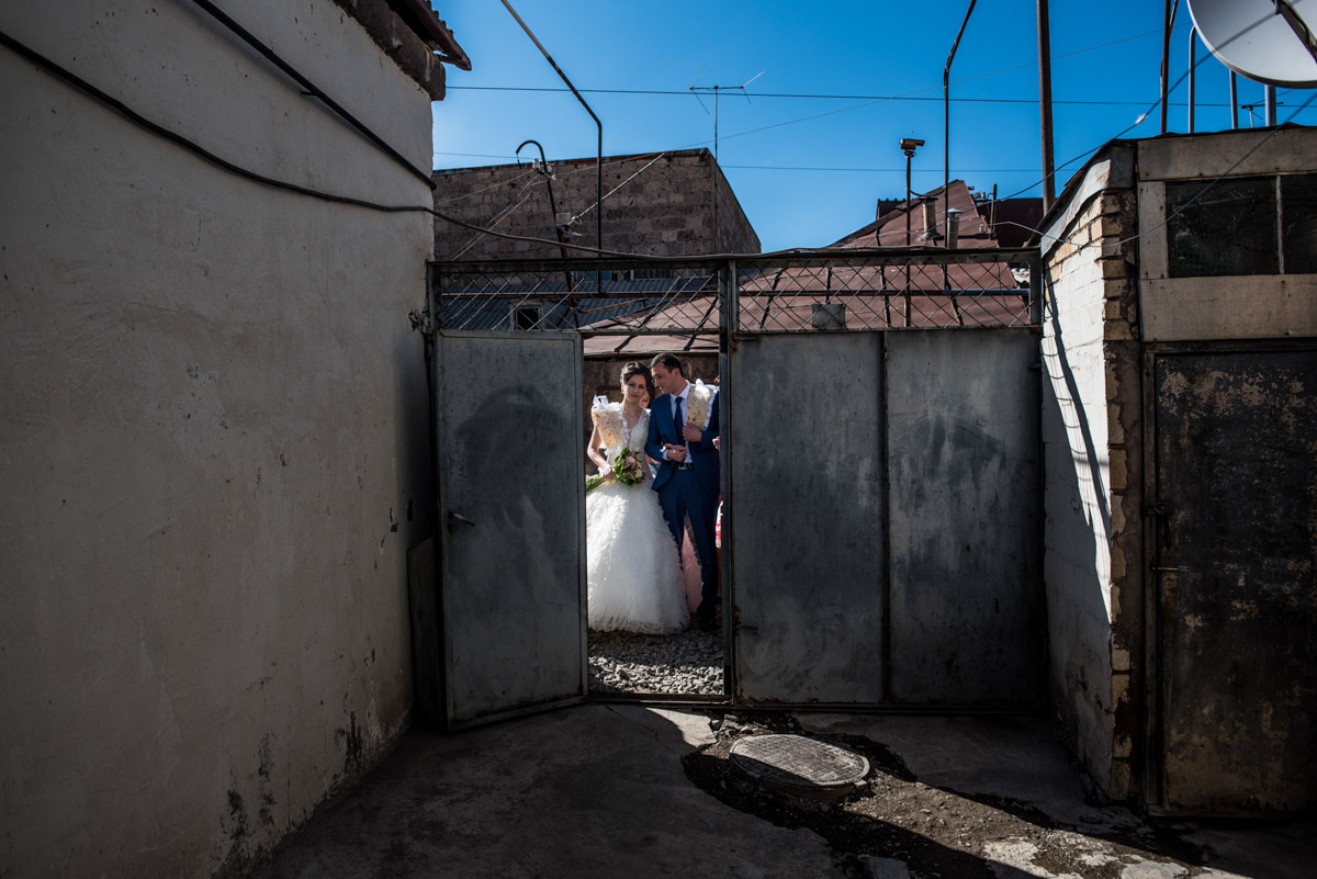 armenian bride and groom are photographed at the door to their home on their wedding day