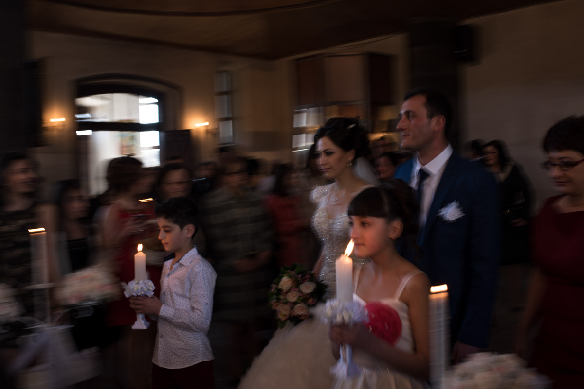 Armenian bride and groom walk up the church aisle with children holding candles