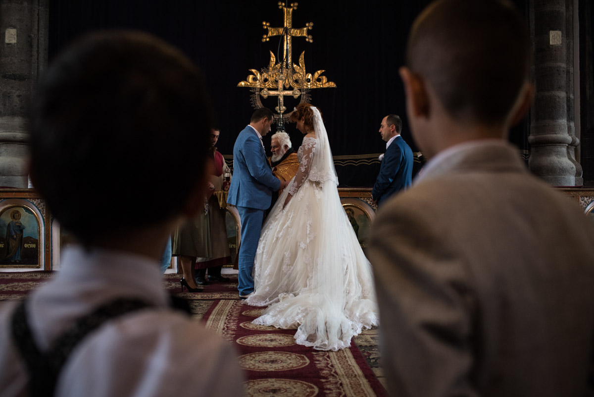 Photograph from the back of the church of armenian bride and groom taking their wedding vows