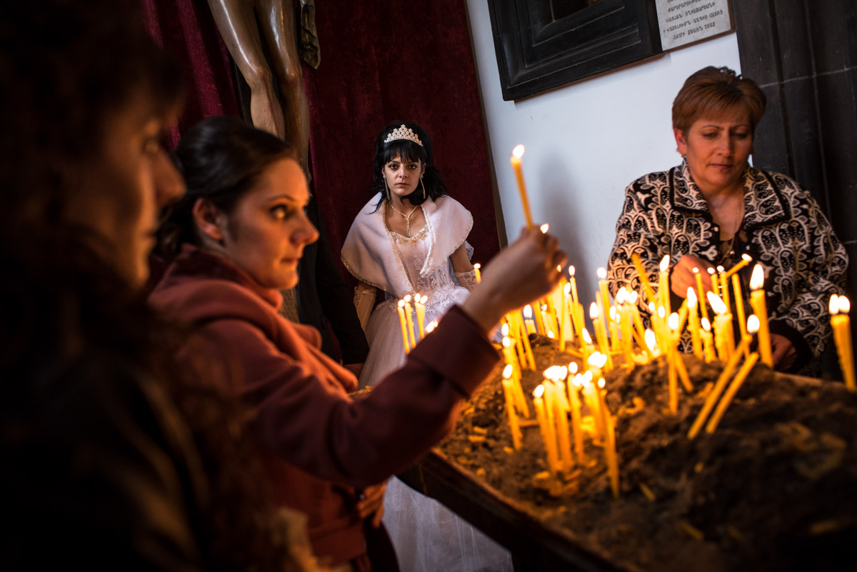 Photograph of sad looking armenian bride as church goers light candles