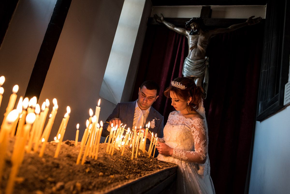 armenian bride and groom light candles on their wedding day with sculpture of christ behind them