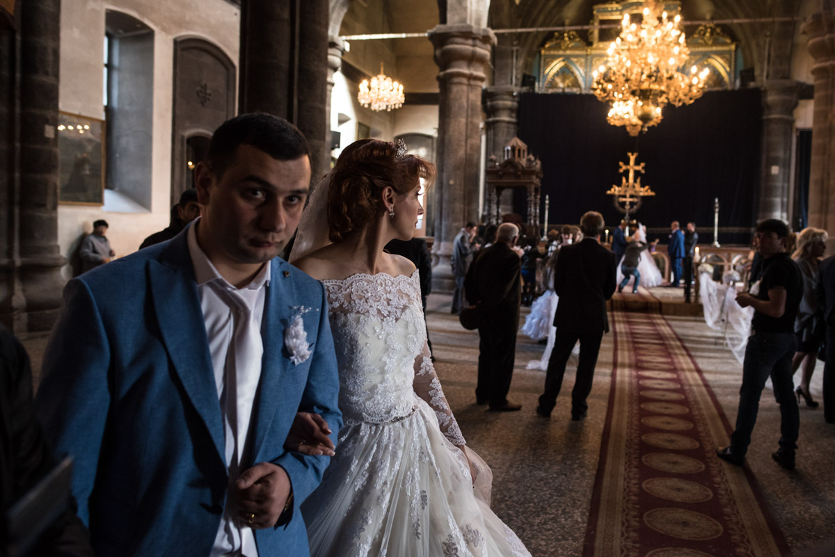 photograph of bride and groom leaving armenian church while another couple are getting married