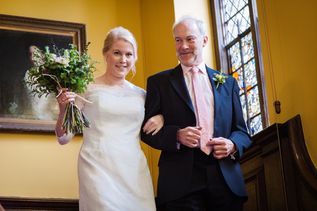 Father and bride walk down stairs at Boughton Monchelsea for wedding ceremony