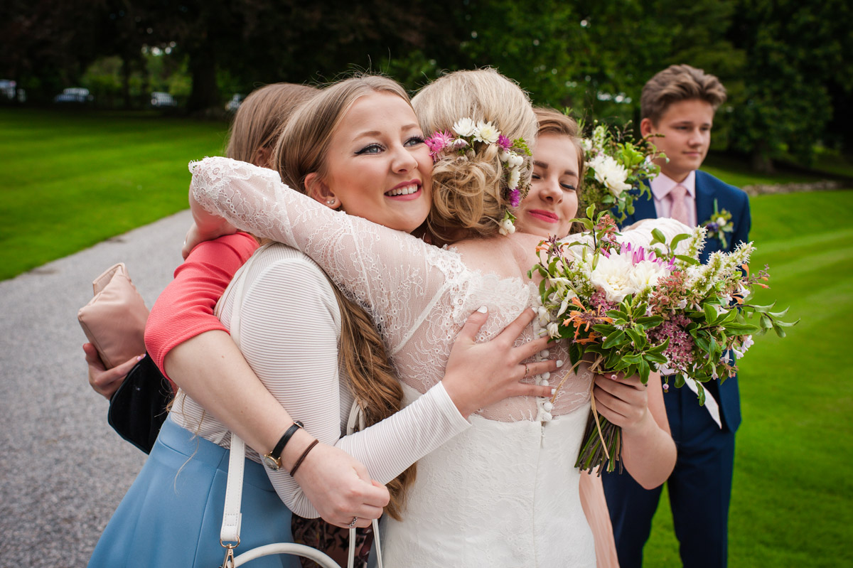 Wedding guests are photographed hugging bride after wedding ceremony at Kent wedding venue Boughton Monchelsea Place