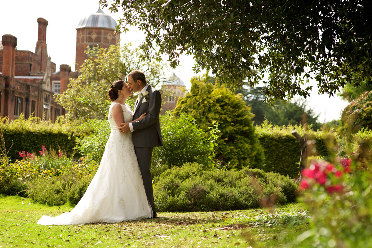 Photograph of andrea and tim on their wedding day with cobham hall in kent in the background