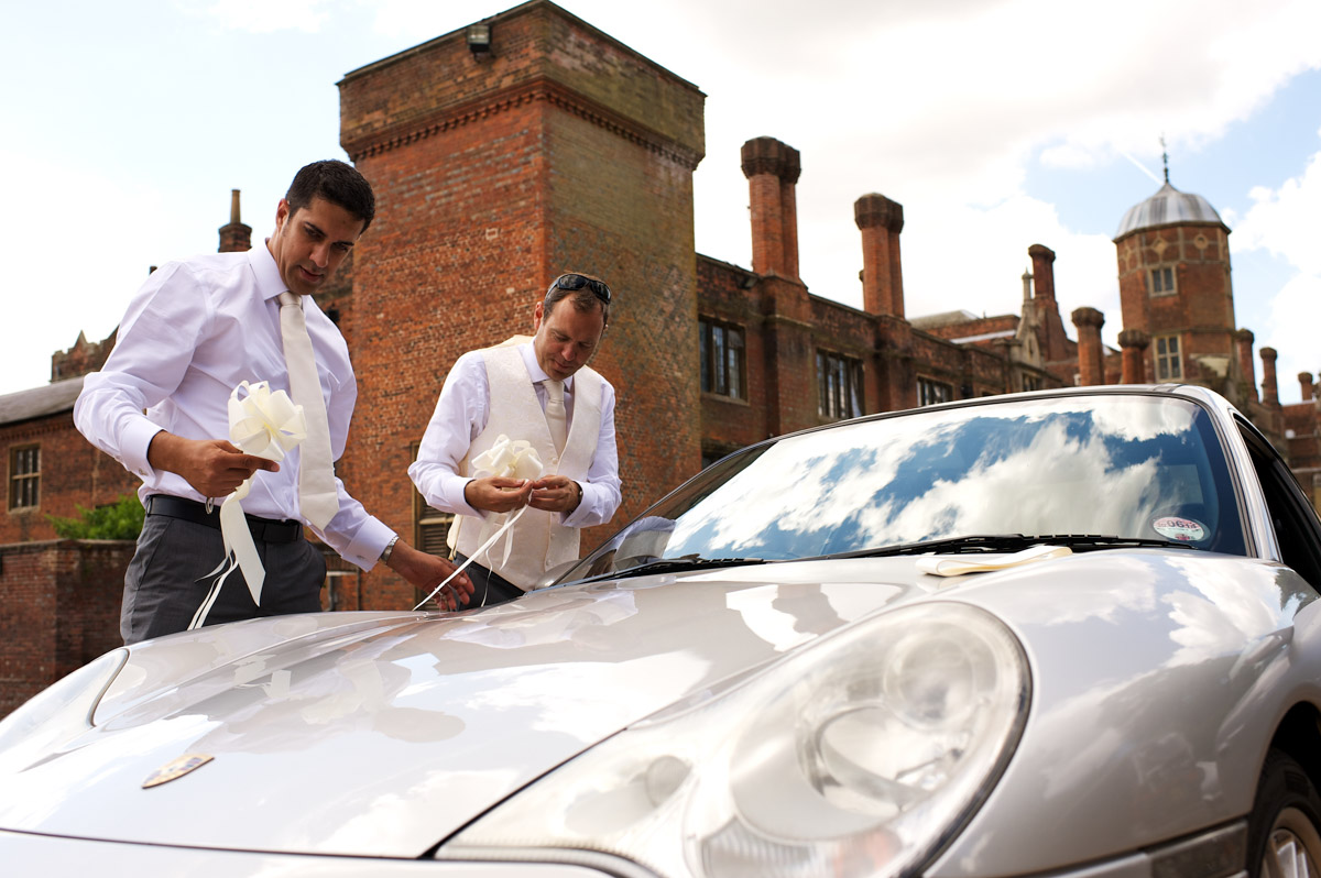 Tim and his best man put ribbons on the wedding car outside cobham hall