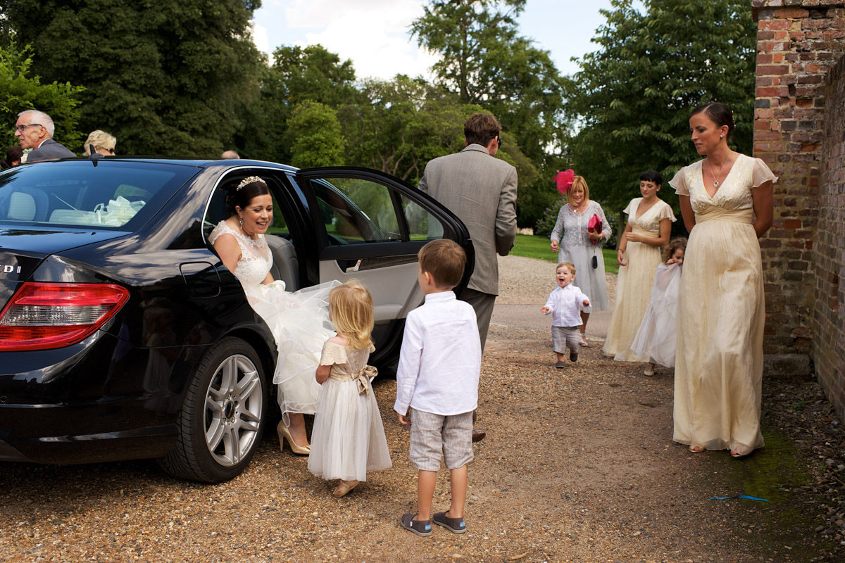 Andrea steps out of the car at cobham hall on her wedding day
