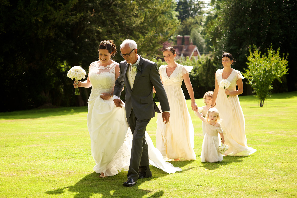 Andrea and her father and bridesmaids walk across the lawn at cobham hall on her wedding day