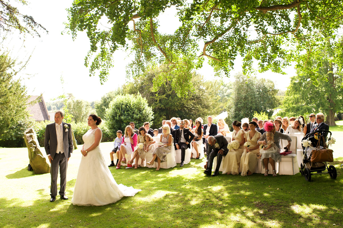 Tim and Andrea during their outdoor wedding at cobham hall looked on by their wedding guests