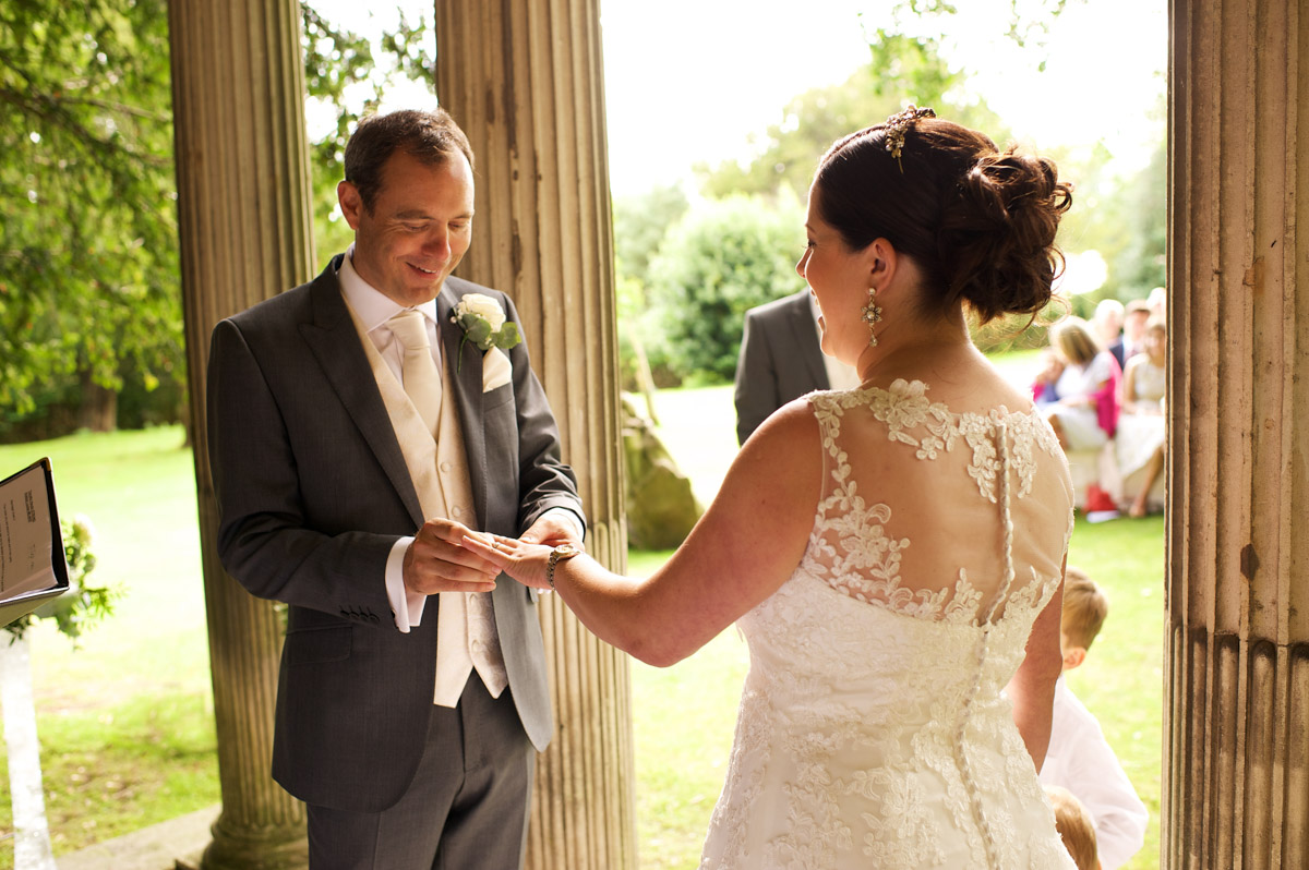 Tim puts the wedding ring on andreas finger during their cobham hall wedding ceremony
