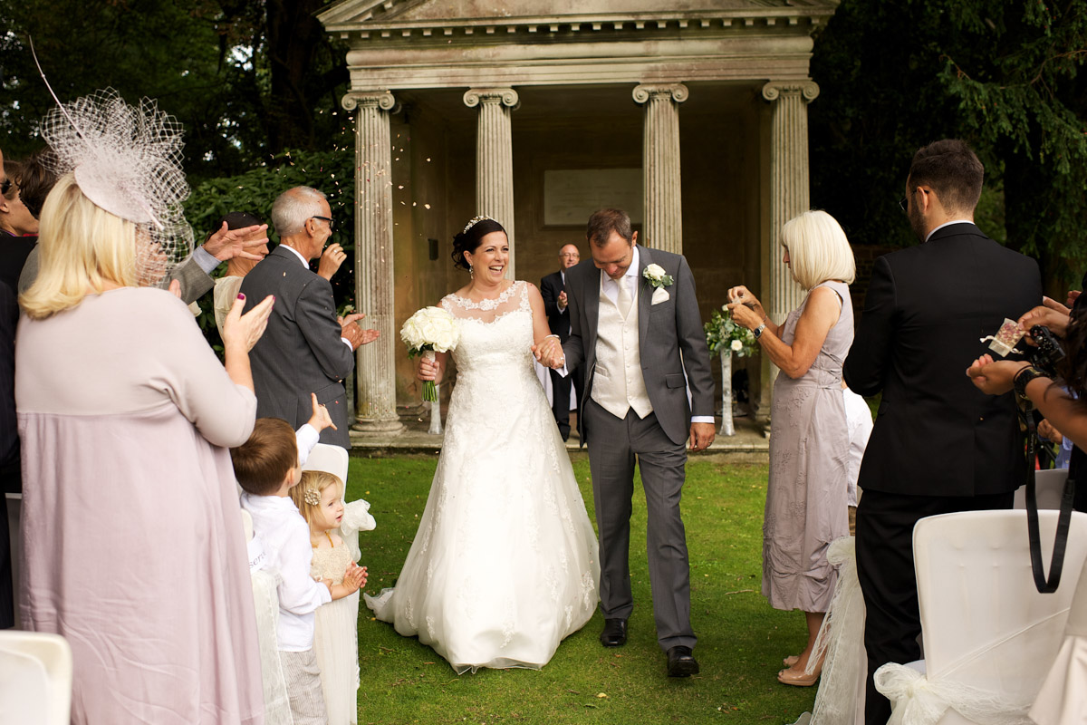 andrea and tim have confetti thrown on them at cobham hall