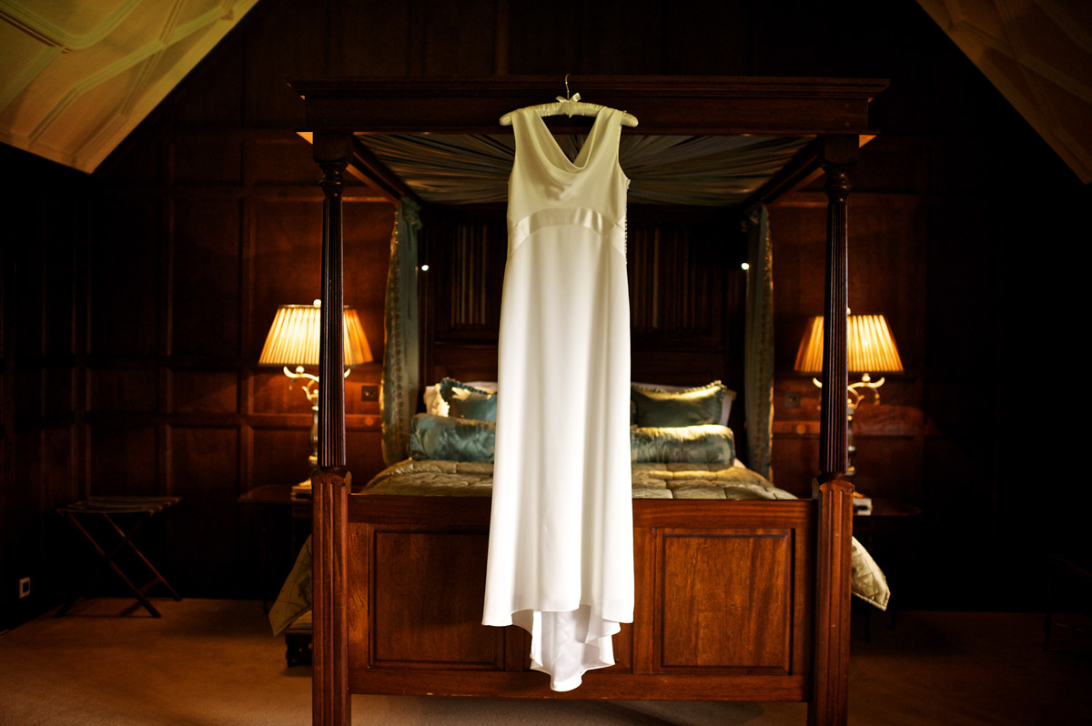 photograph of gains wedding dress hanging up on the bed in Hever castle