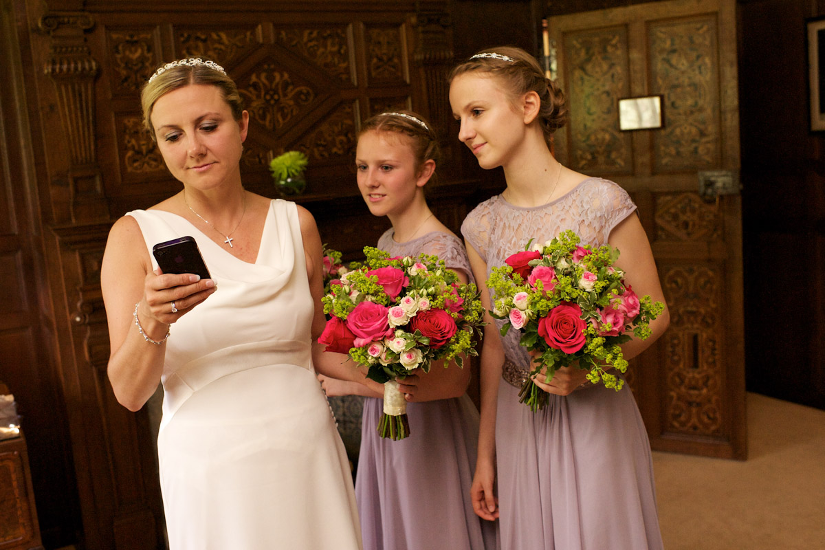 bride looks at her phone with her bridesmaids before her ceremony at never castle