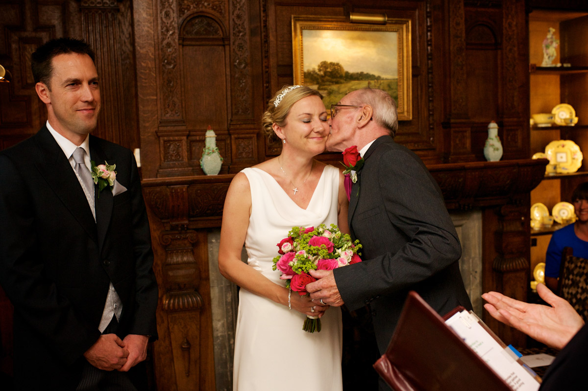 gail dad kisses her cheek as he gives her away during her wedding ceremony at never castle in kent