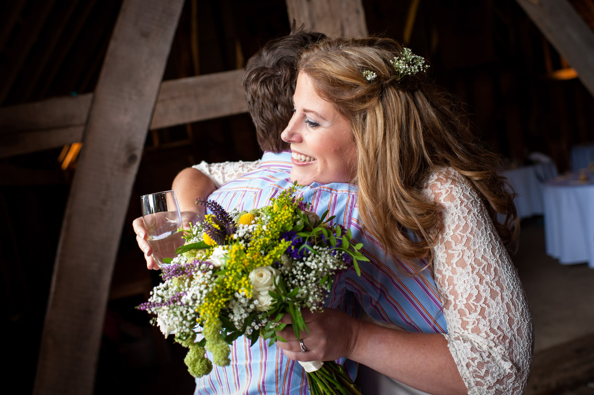Corinne hugs guest at Ratsbury Barn wedding