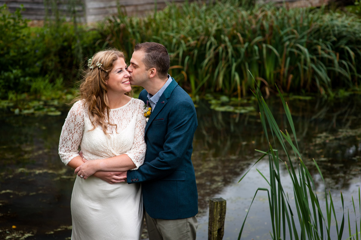 Photograph of Corinne and Doug by pond at Ratsbury barn after their wedding ceremony photographed by Helen Batt
