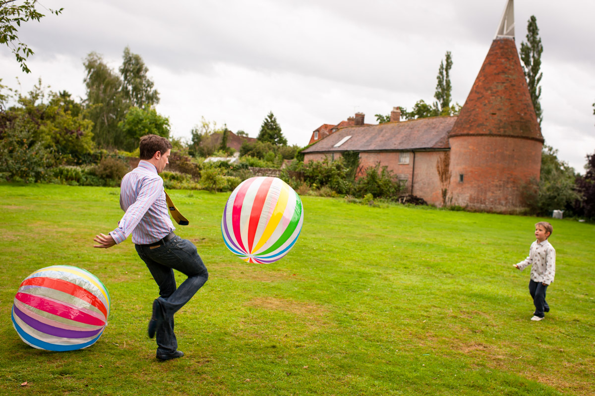 adult and children photographed playing with ball at Ratsbury barn wedding in Kent