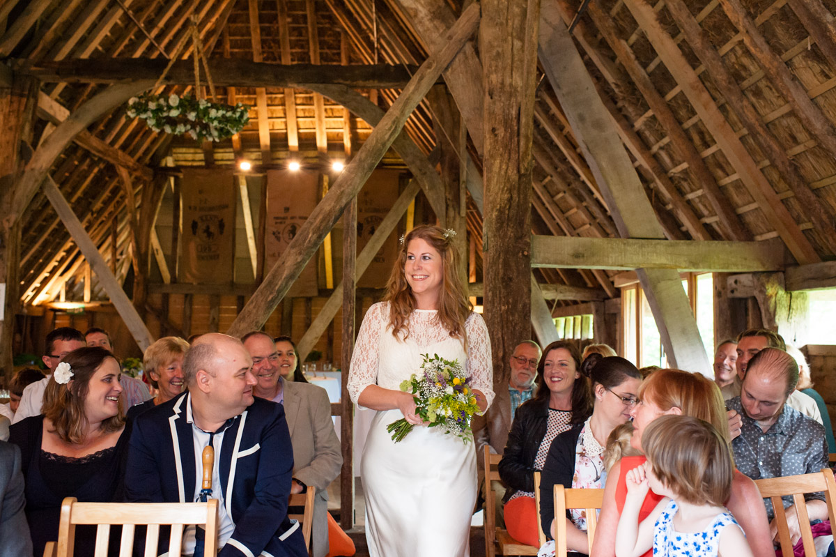 Ratsbury Barn wedding photography of Corinne walking up the aisle for her wedding ceremony in rats bury Barn in Kent