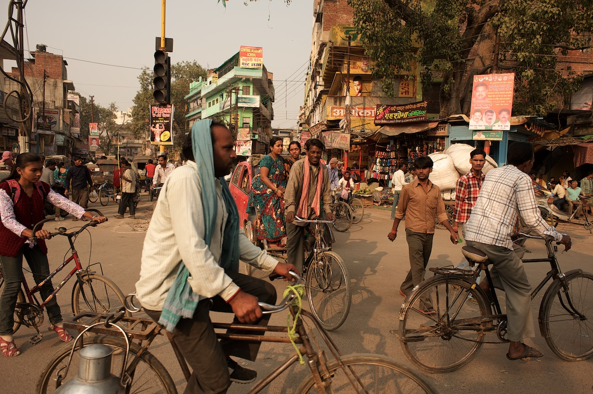 Photograph of people riding bicycles and walking in streets of varanasi