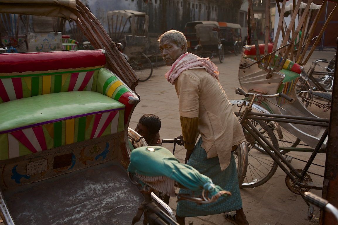 Photograph of rickshaws and people in India
