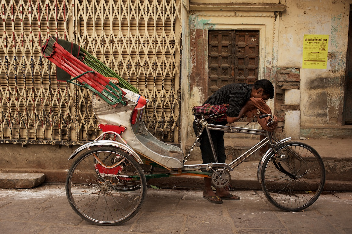 photograph of man wiping sweat from his face by his rickshaw