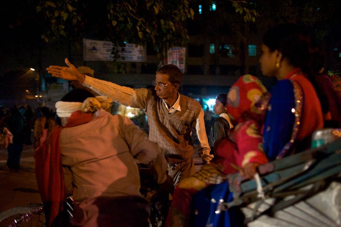 man indicates directions with his arm in traffic in varanasi