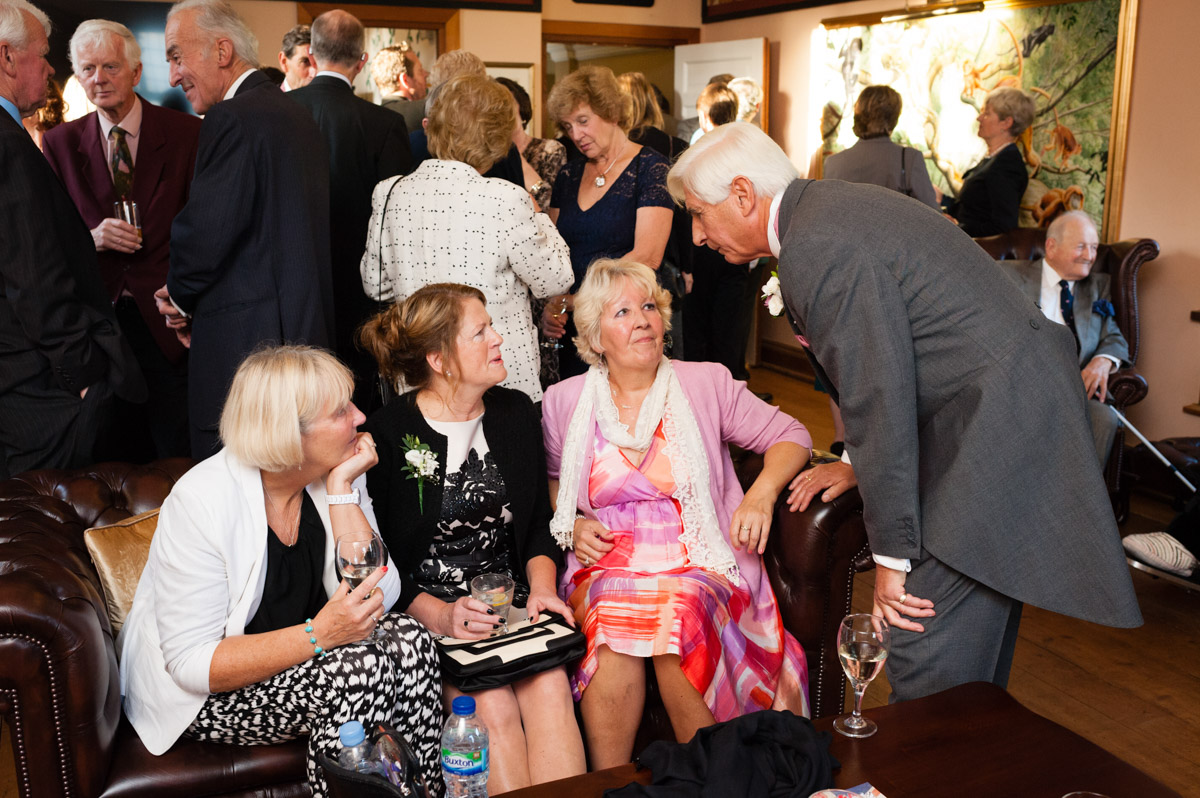 Dick talks to wedding guests in the bar at port lymph mansion wedding venue