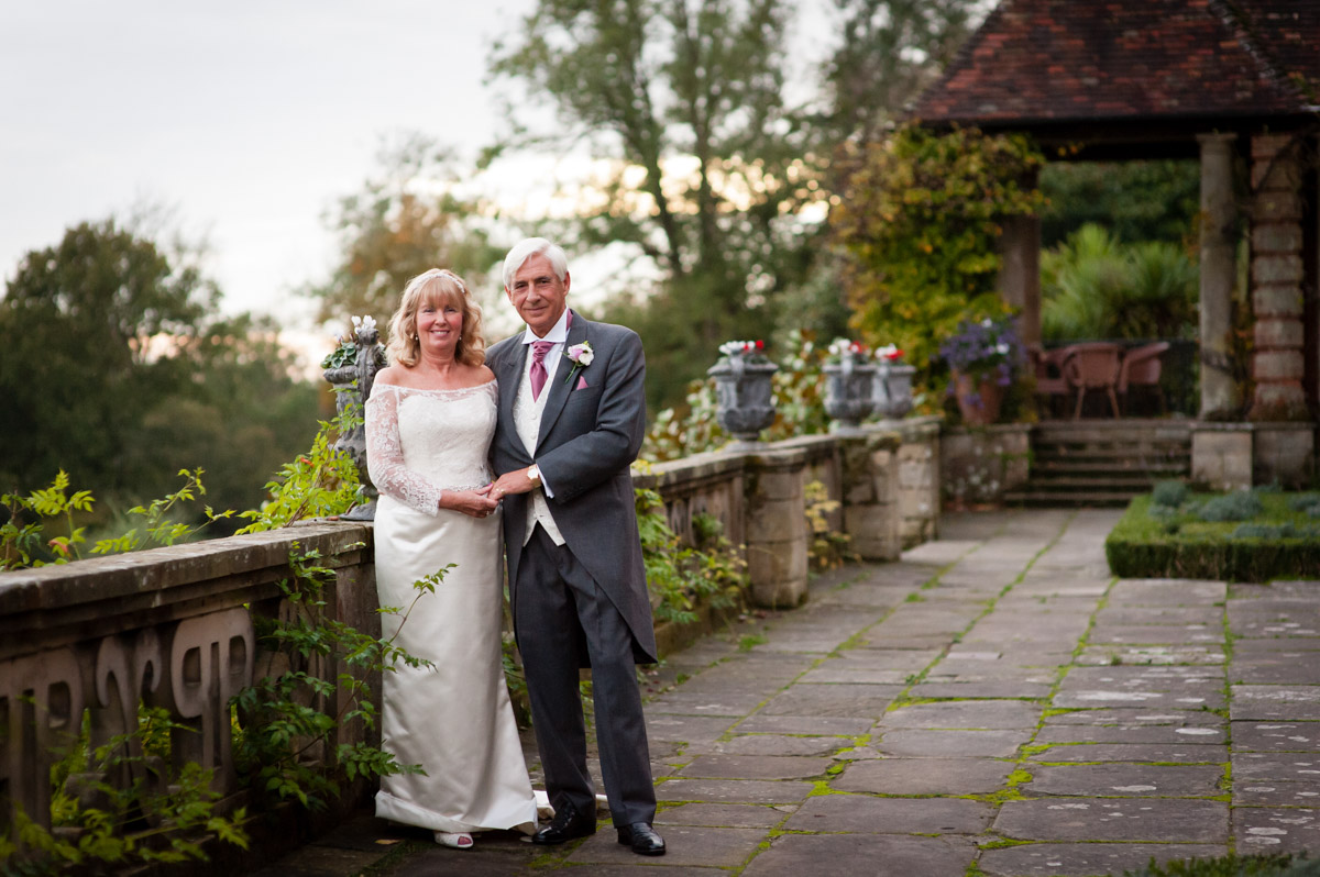 martine and dick photographed on the verander at port lymph mansion on their wedding day