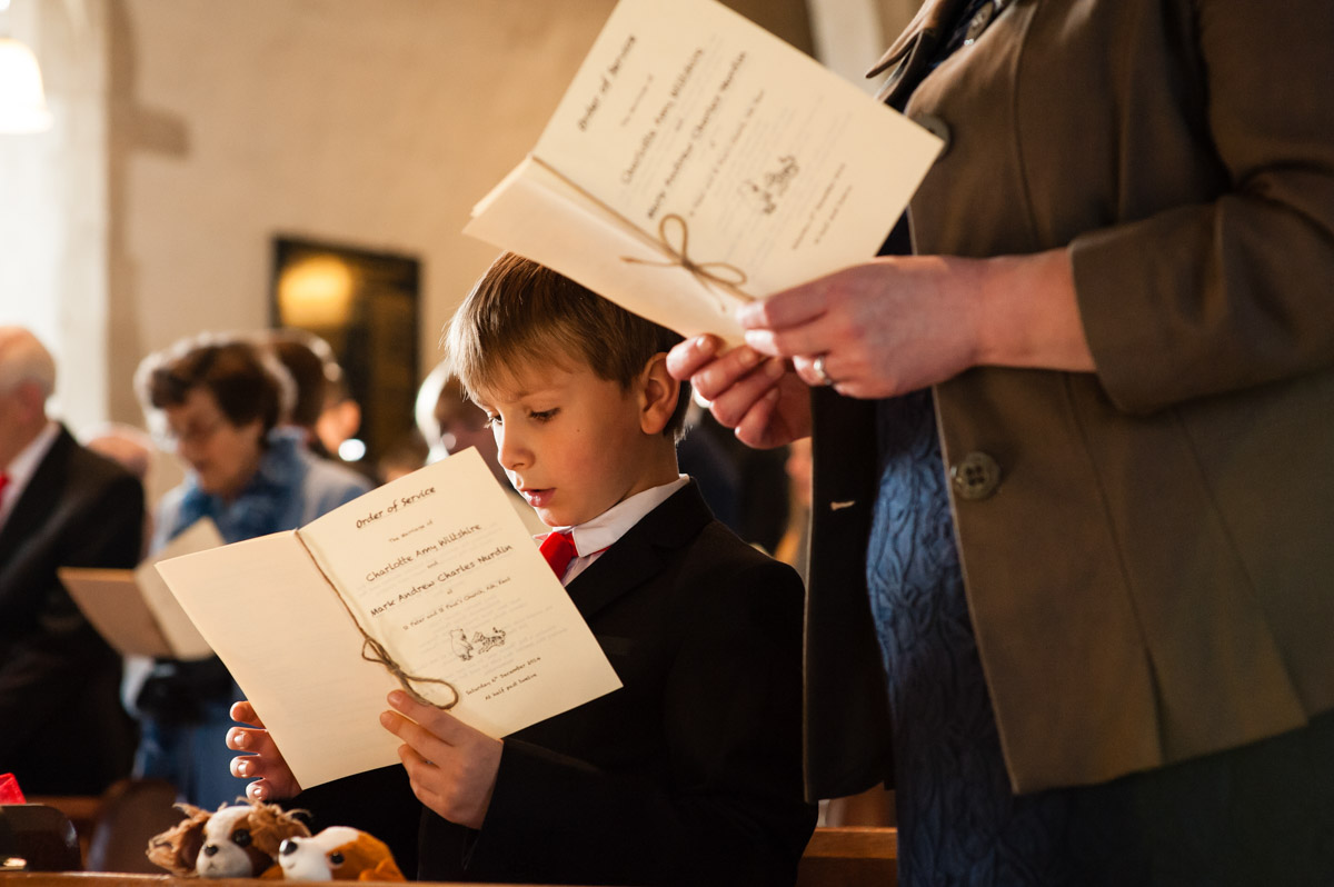 pageboy sings from order of service during charlotte and marks church wedding in kent