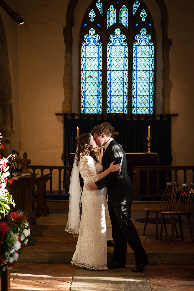 charlotte and marks first kiss after their winter church wedding in kent