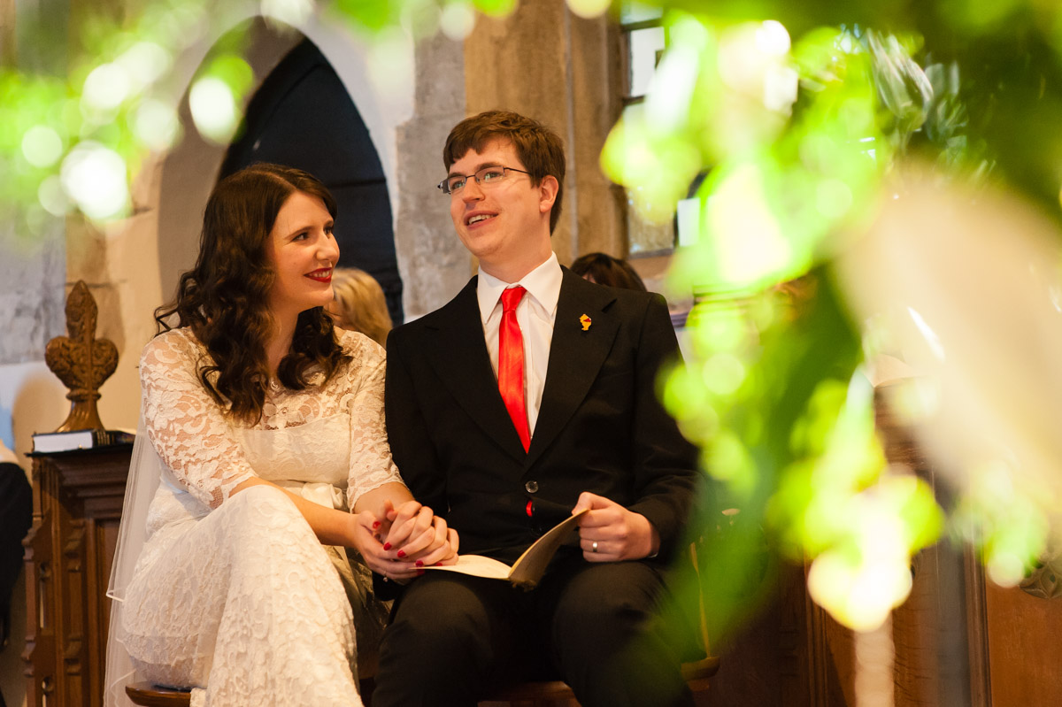 photograph of charlotte and mark listening to vicars address during their kent wedding