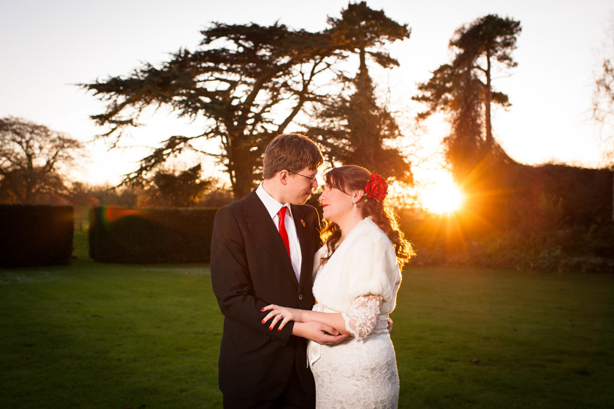 sunset photograph of charlotte and mark in garden at nursted court during their kent winter wedding reception