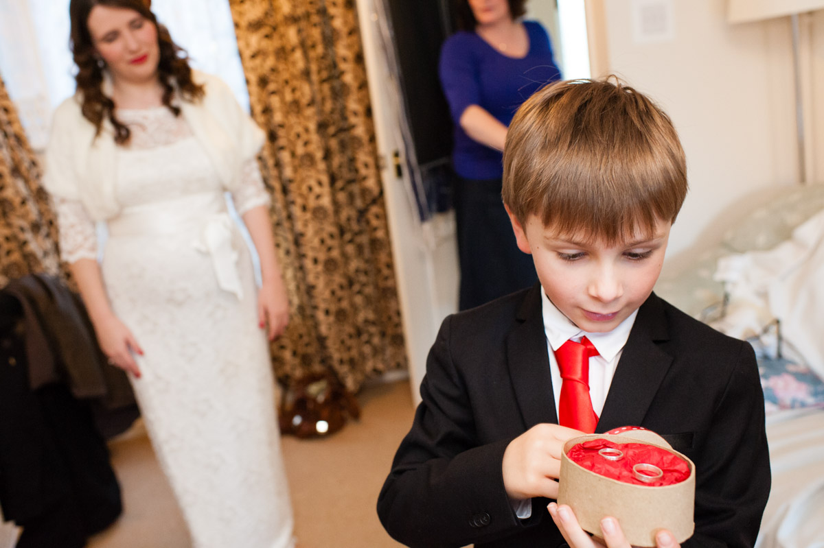 page boy looks at wedding rings