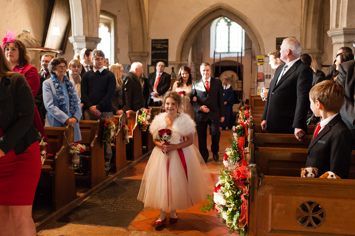 flower girl walks up church aisle followed by charlotte and her dad