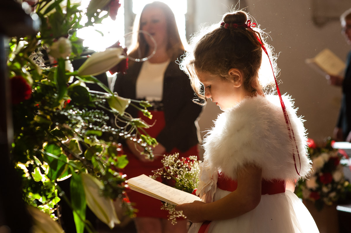 photograph of flower girl at charlotte and marks church wedding lit by sun through window