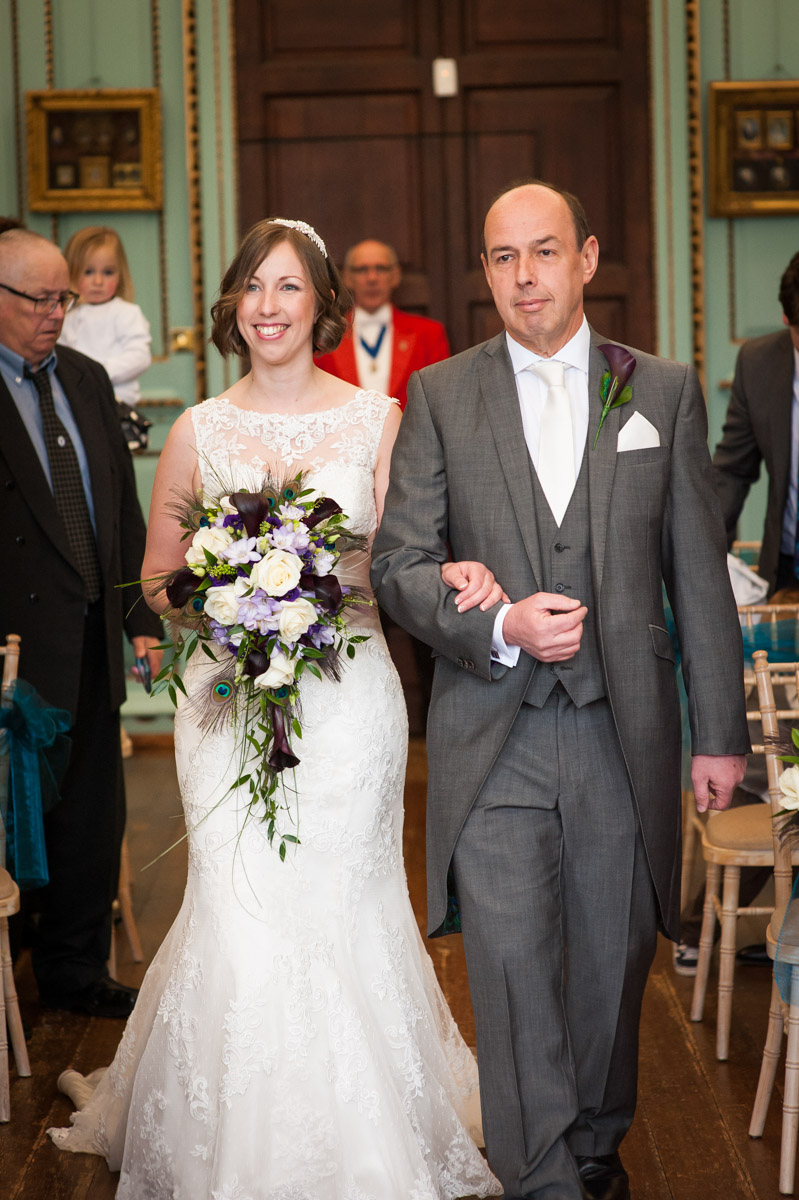 The bride is walked into The Great Hall at Bradbourne House by her father