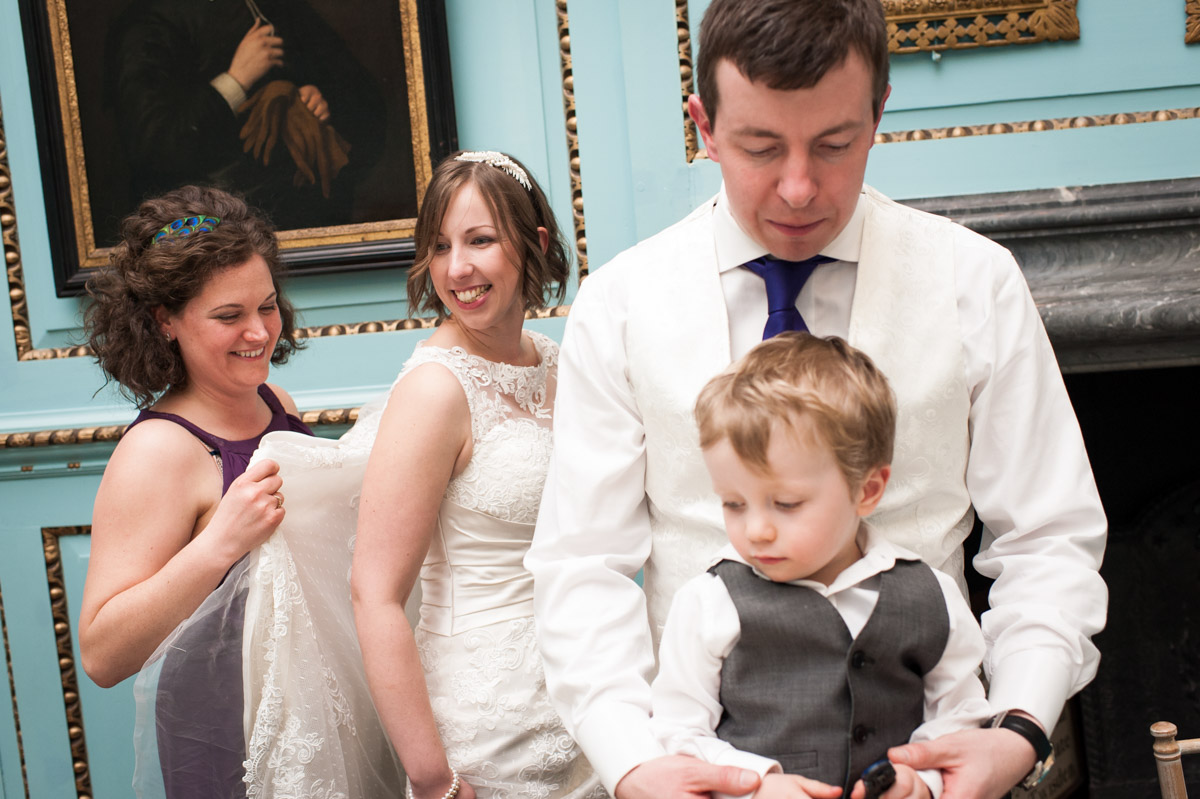 Brdie is helped with her dress by bridesmaid before the wedding reception in the Great hall at Bradbourne House