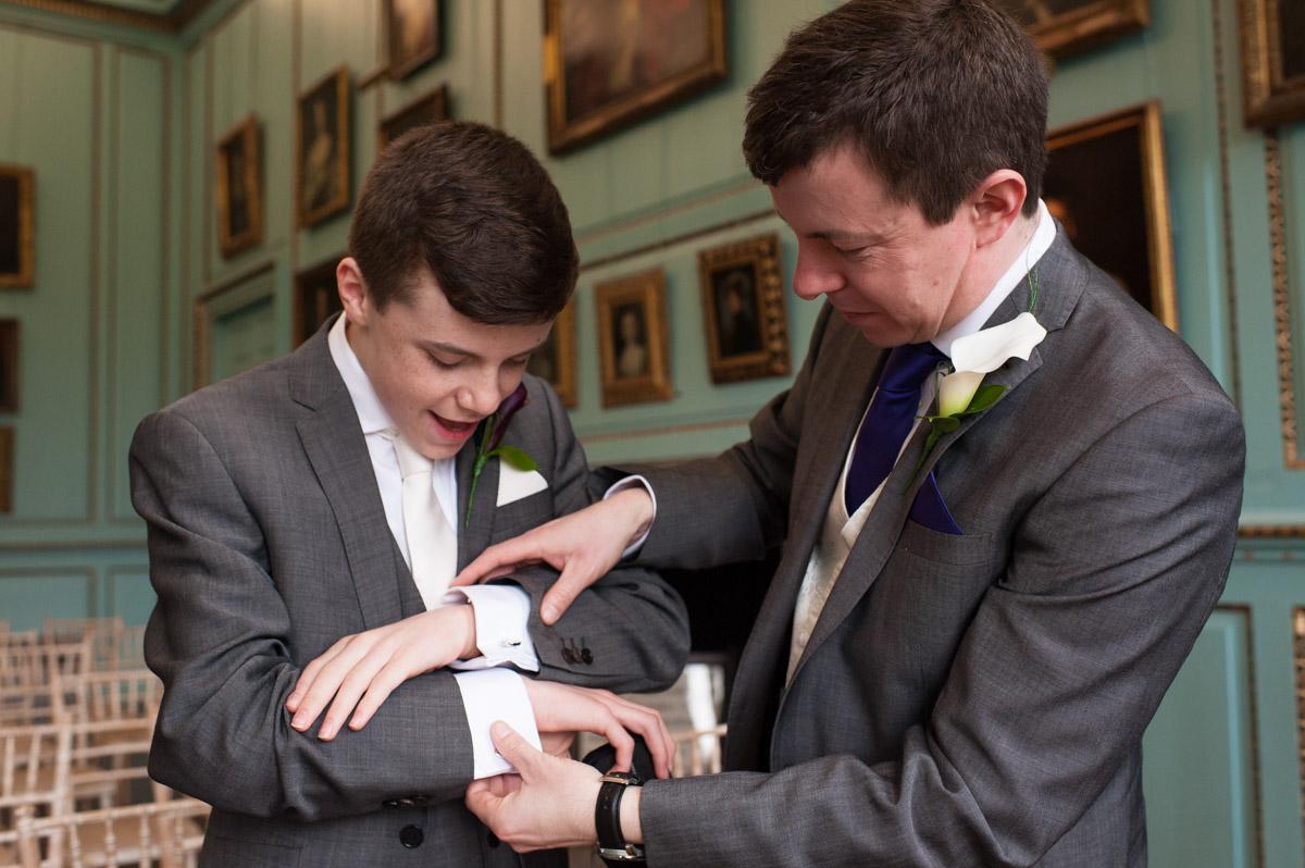 Groom and his groomsman fix cufflinks before the wedding ceremony at Bradbourne House