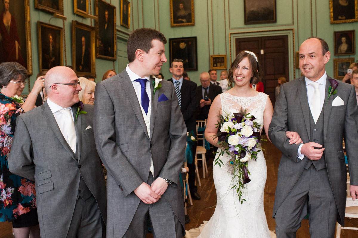 The groom looks at his bride as she walks up the aisle at Bradbourne House wedding