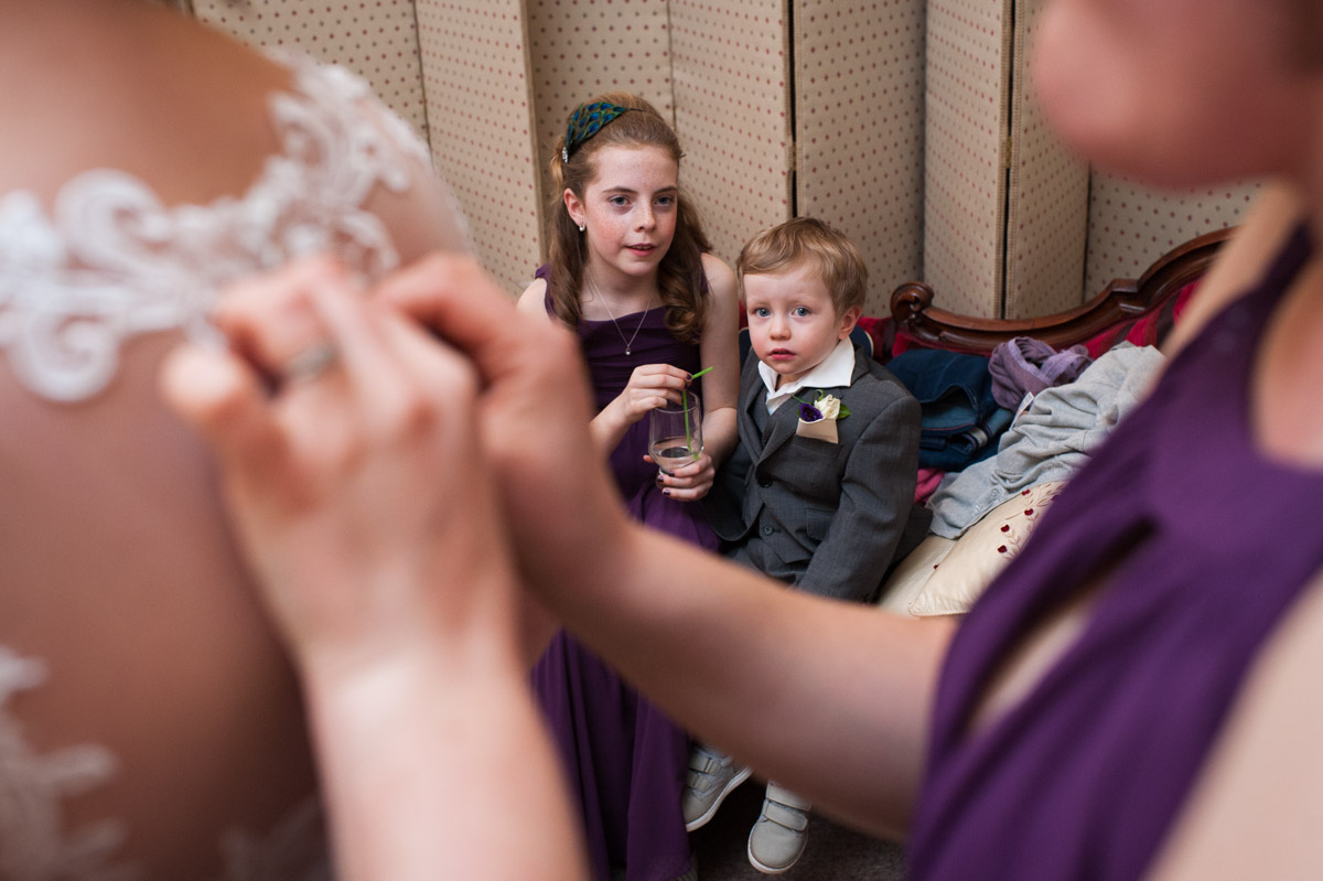 Page boy and flower girl watch the brides dress being fastened by the bridesmaid