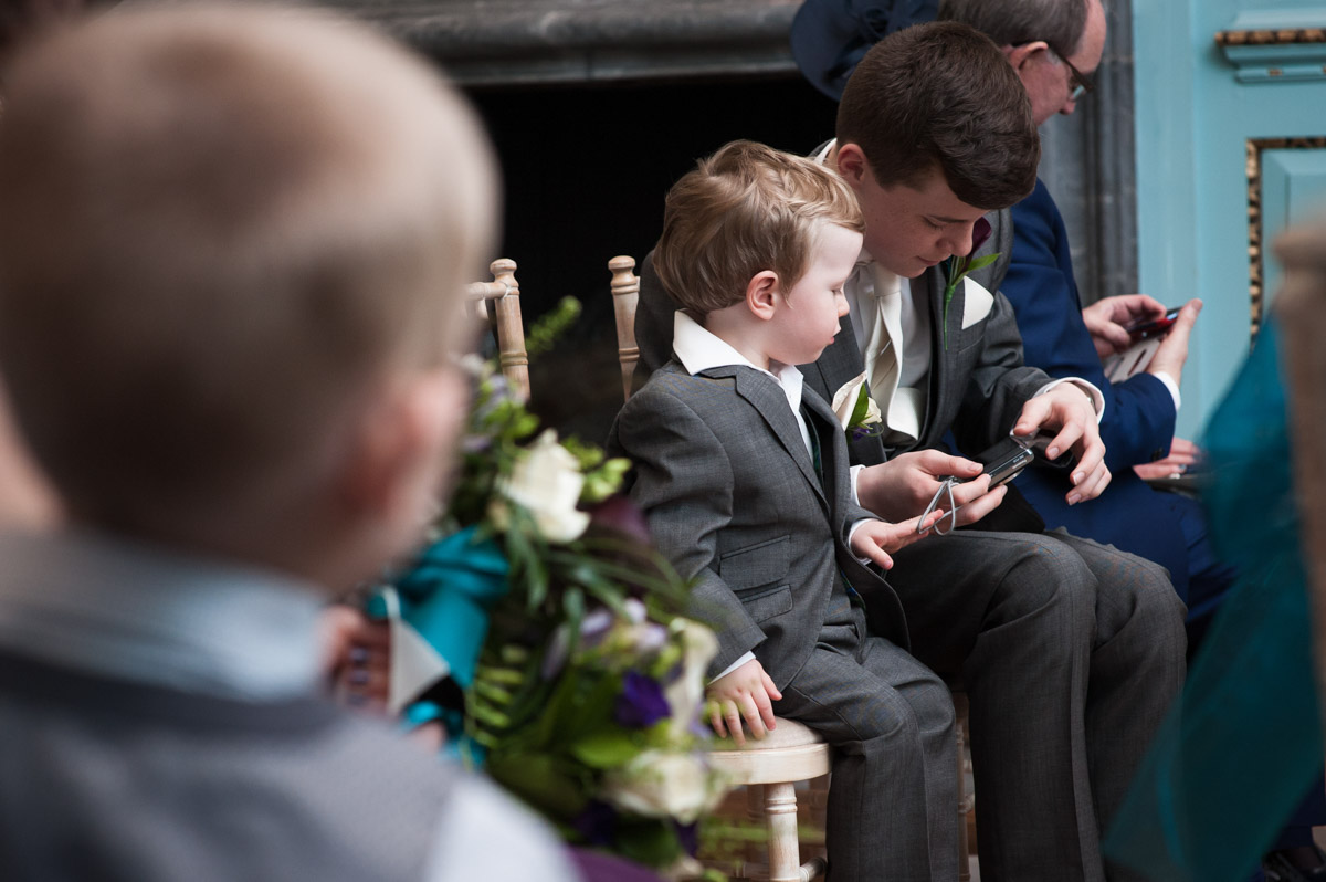 Two pageboys play with their camera after the wedding ceremony