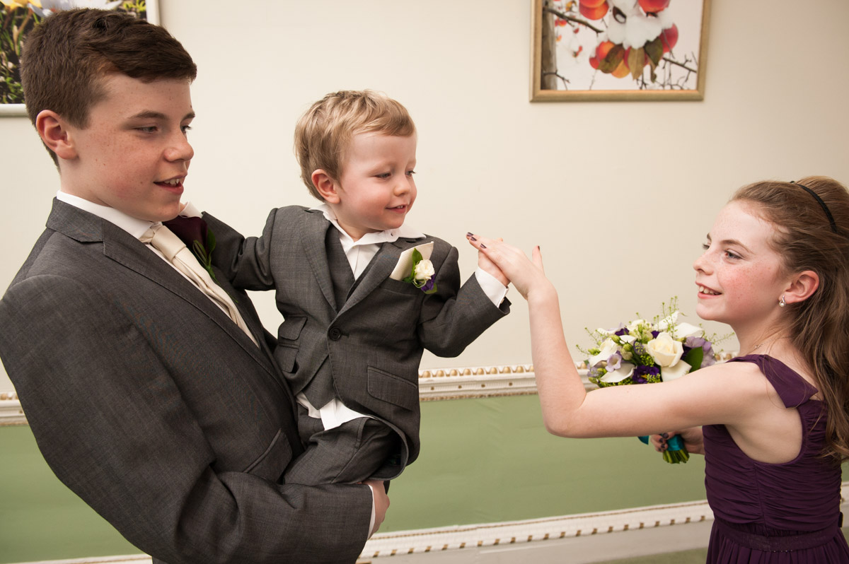 Young pageboy enjoys some fun with his sister at the wedding of his mum and dad