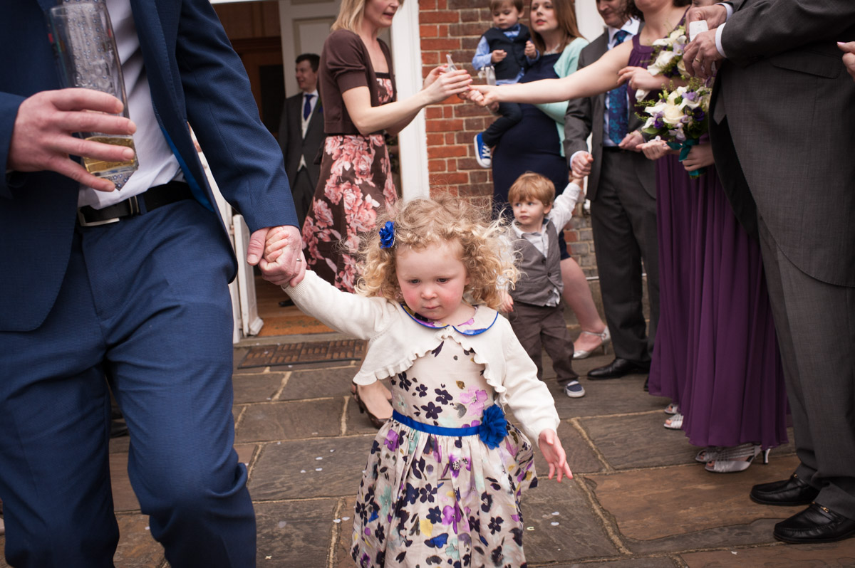 Guests at a wedding at Bradbourne House prepare for the confetti photo outside on the steps