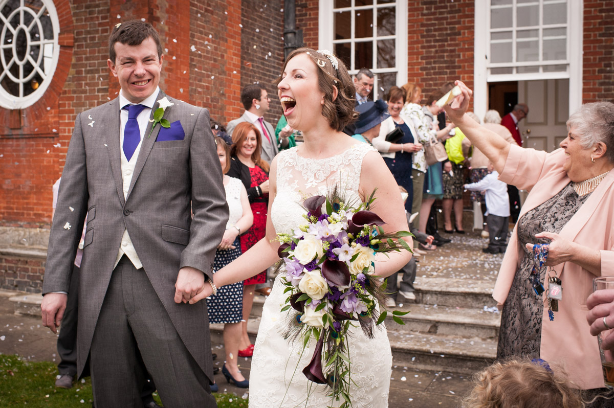 The newly married couple have confetti thrown on them by guest at Bradbourne House