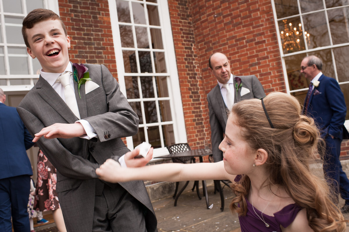 Brother and sister mess about after the confetti photo at Bradbourne House