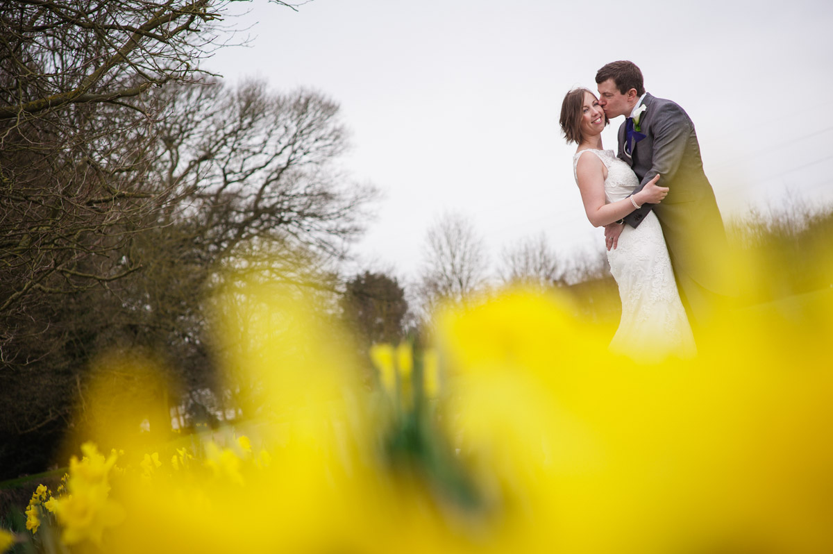 Portrait of the wedding couple at Bradsbourne House outside with daffodils in the foreground
