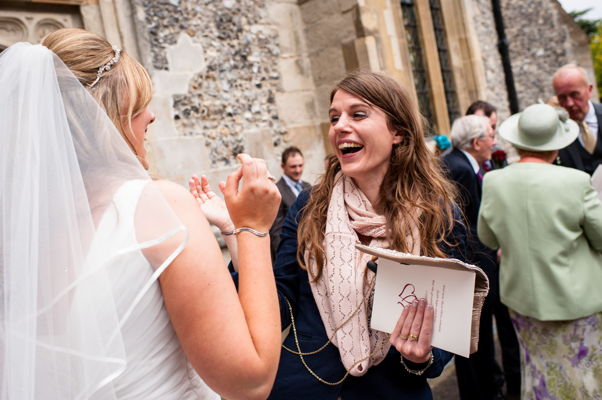 Wedding guest laughs with bride outside church after wedding