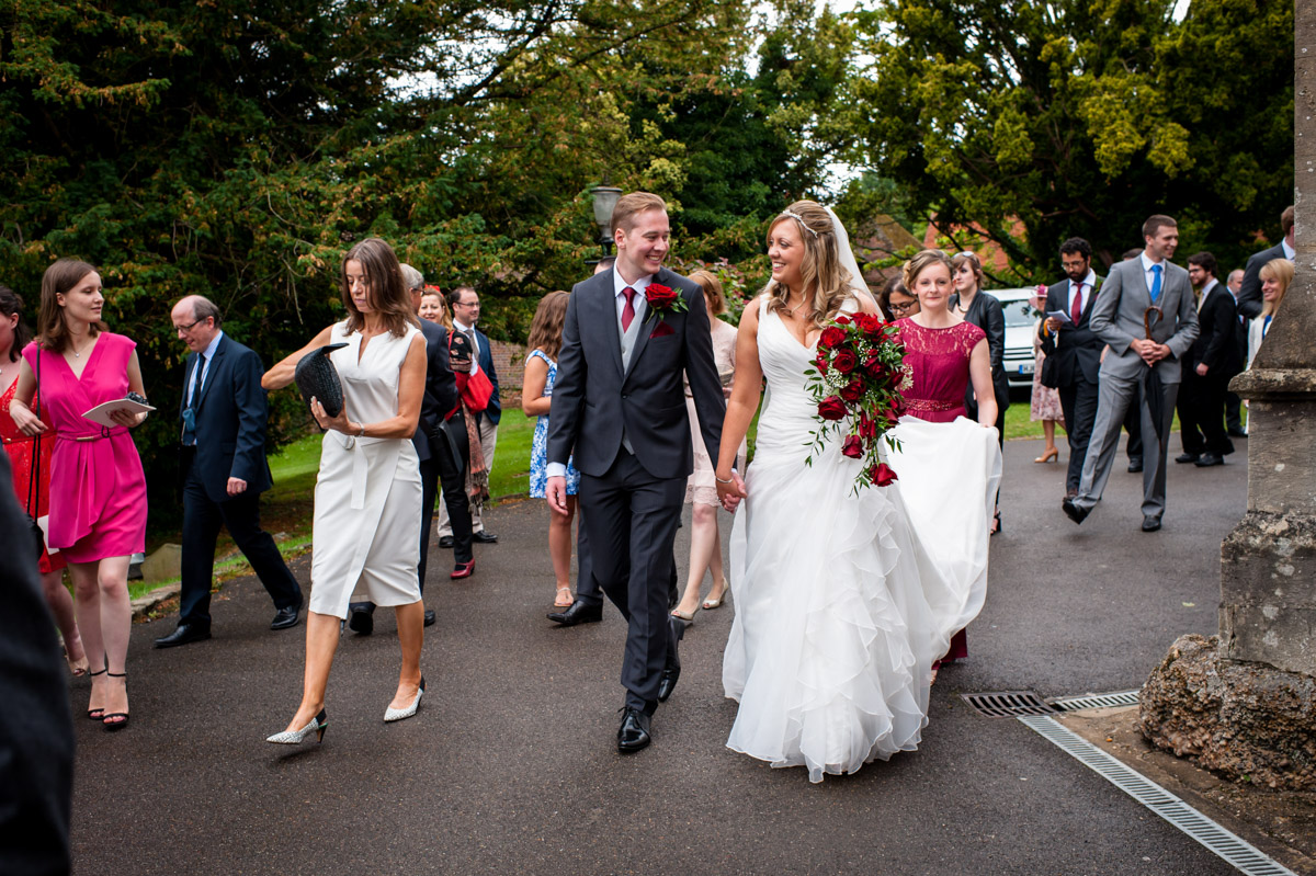 Photo of bride and groom walking down church path with wedding guests